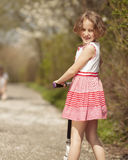 Young girl riding scooter in park away from camera to mother Stock Images