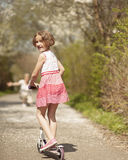 Young girl riding scooter in park away from camera to mother Royalty Free Stock Photo