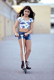 Young girl riding scooter Stock Image