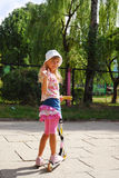 Young girl riding scooter  waving hand to friends Royalty Free Stock Images