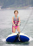 Young Girl riding a ski tube behind a boat Royalty Free Stock Photos
