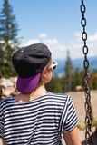 A young girl is riding on a swing overlooking the mountains Royalty Free Stock Photos