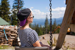 A young girl is riding on a swing overlooking the mountains Royalty Free Stock Photography
