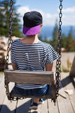 A young girl is riding on a swing overlooking the mountains Stock Photo