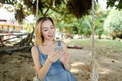 Young girl riding swing and using smatrphone, sand and tree in background. stock photography