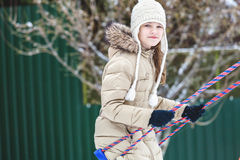 Young girl riding on swing in winter Stock Photography