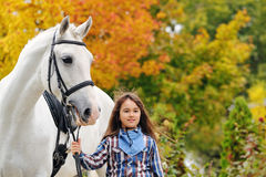 Young girl riding on white dressage horse Royalty Free Stock Image