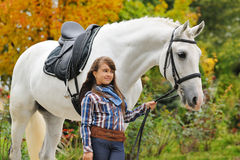 Young girl riding on white dressage horse Stock Image