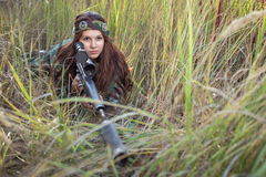 Young girl with a rifle peeking out of the grass. Young girl with a rifle playing laser tag Royalty Free Stock Photography