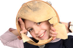 Young girl with ripped tambourine. Smiling young girl peeking through a ripped tambourine Royalty Free Stock Image