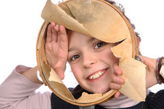 Young girl with ripped tambourine. Smiling young girl peeking through a ripped tambourine Royalty Free Stock Photography