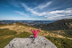 Young girl rises up her hands while sitting on top of cliff on mountain background. Young girl rises up her hands while sitting on top of cliff on mountain and stock image