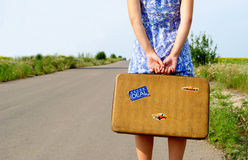 Young girl on the road with a suitcase Royalty Free Stock Photography