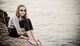 Young girl on a rock. Young girl sitting on a rock by the ocean Stock Images