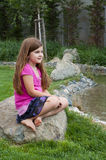 Young Girl on Rock by Calm Stream Stock Images