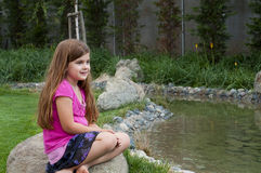 Young Girl on Rock by Calm Stream Royalty Free Stock Photography