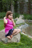 Young Girl on Rock by Calm Stream Stock Image