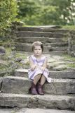 Young girl on rock steps looking bored. Young girl with short hair sitting on rock steps. Little girl looks bored. She is wearing a dress and boots Royalty Free Stock Image