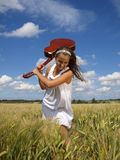 Young girl rocking guitar. Young girl in white dress in the field is rocking guitar Stock Photo