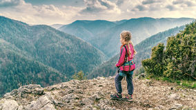 Young girl on a rocky clif. Young girl wearing mountain climbing harness standing on a rocky clif and looking on a distant hills Royalty Free Stock Photos