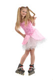Young  girl on roller blades. A view of a cute blond adolescent girl wearing a pretty pink and white party dress and roller blades, isolated on a white Royalty Free Stock Photo
