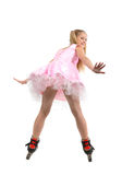 Young  girl on roller blades. A view of a cute blond adolescent girl wearing a pretty pink and white party dress and roller blades, isolated on a white Royalty Free Stock Image