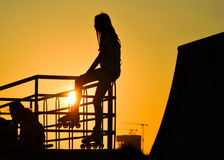 Young girl roller skater sitting on the fence at sunset, silhouette. royalty free stock images