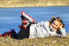 Young girl in roller skates lays on the ground Stock Images