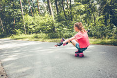 Young girl roller skating down on a forest road Royalty Free Stock Photography