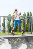 Young girl in rollerblades on a ramp Stock Photo