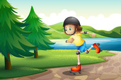 A young girl rollerskating at the riverbank with pine trees Stock Images