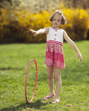 Young girl rolling hula hoop in park Royalty Free Stock Image