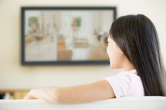 Young girl in room with flat screen television royalty free stock image
