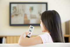 Young girl in room with flat screen television Royalty Free Stock Photo