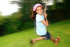 Young girl on rope swing. Young girl swinging fast on the rope swing tied to a tree, enjoying the outdoors royalty free stock photography