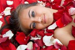 Young girl in rose peta. Beautiful young girl in rose petal. Spa resort Stock Photo