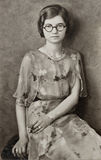 Young Girl with Round Glasses. Early 1990s sepia-toned photograph of a young girl Royalty Free Stock Image
