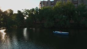 Young girl rowing in a boat on the lake. High-rise buildings around the lake. Trees grow along the shores of the city lake. View from above stock footage