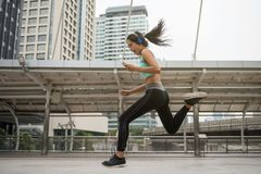 Young girl run and exercise in city. Portrait of Beauty Asian young woman with sport cloth jump while listen music by smartphone with Modern Bangkok building Stock Photo