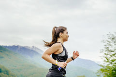 Young girl runner with energy nutrient gel in hand running Royalty Free Stock Images