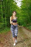 Young girl runner in the forest Royalty Free Stock Photos