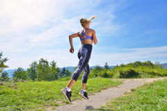 Young girl runner jogging on a mountain trail in the beautiful landscape. Stock Photo