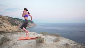 Young girl runner training at sunrise on a cliff above the ocean. Preparation for a morning run, athlete in top and. Leggings 4k stock footage