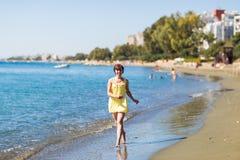 Young girl running along the beach of a sea. Stock Photos
