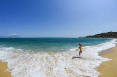 Young girl running along the beach Royalty Free Stock Photos