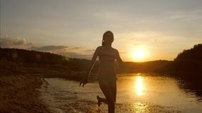 Young girl running along beach splashing water from under her feet, beautiful sunset over the river, slow motion. Young girl running along beach splashing water stock photo