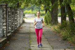 Young  girl running along the path in the Park. Stock Photo