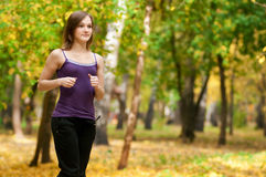 A young girl running in autumn park Stock Photo