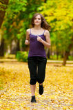 A young girl running in autumn park Stock Image