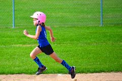 Young Girl Running Bases in Softball. She is digging hard for third base Stock Image